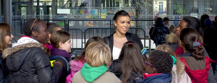 Une professeure accueillant ses élèves de collège